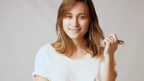 Giovane donna attraente allegra che posa, flirtando, sorridere, giocante con i capelli stock footage