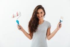 Giovane donna attraente allegra con il rullo di pittura e della spazzola immagini stock libere da diritti