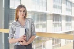 Giovane donna attraente allegra con lo zaino ed i taccuini che stanno e che sorridono nell'università, collage Giovane bionda Fotografie Stock Libere da Diritti