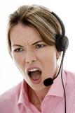 Giovane donna attraente arrabbiata di affari che per mezzo di una cuffia avricolare del telefono Immagine Stock