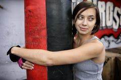 Giovane donna attraente che abbraccia punching ball Immagini Stock Libere da Diritti