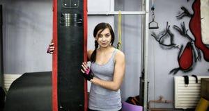 Giovane donna attraente che abbraccia punching ball Immagine Stock