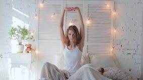 Giovane donna attraente che allungano a letto di mattina e sorridere video d archivio