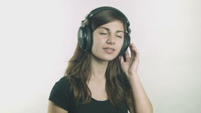 Giovane donna attraente che ascolta la musica sulle cuffie video d archivio