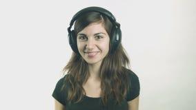 Giovane donna attraente che ascolta la musica sulle cuffie archivi video