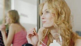 Giovane donna attraente che ascolta la musica sulle cuffie, mangianti riso con i bastoncini in una scatola di carta video d archivio
