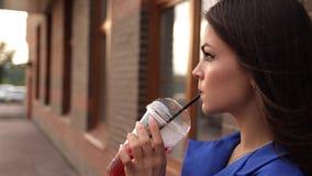 Giovane donna attraente che beve una bevanda di rinfresco mentre camminando giù la via della città video d archivio