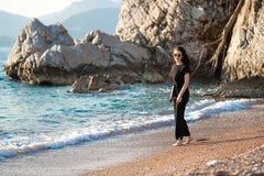 Giovane donna attraente che cammina su una spiaggia soleggiata alla riva Viaggiatore e blogger fotografia stock
