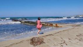Giovane donna attraente che cammina sulla spiaggia di sabbia con il pilastro del mare che porta vestito rosso Forti onde che spru stock footage