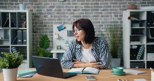 Giovane donna attraente che chiacchiera nello skype facendo uso della tazza della tenuta del computer portatile in ufficio video d archivio