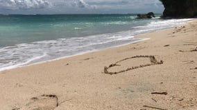 Giovane donna attraente che disegna un cuore sulla sabbia Spiaggia tropicale Isola del Bali, Indonesia stock footage
