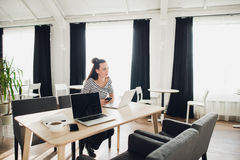 Giovane donna attraente che distoglie lo sguardo meditatamente con il suo computer portatile aperto Immagini Stock