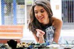 Giovane donna attraente che esamina la finestra del negozio fotografie stock