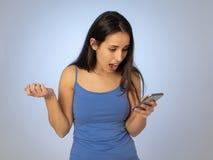 Giovane donna attraente che esamina perdita colpita e sorpresa dello Smart Phone mobile dei simili fotografia stock