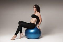 Giovane donna attraente che exersicing con la palla di forma fisica Fotografie Stock