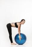 Giovane donna attraente che exersicing con la palla di forma fisica Immagini Stock