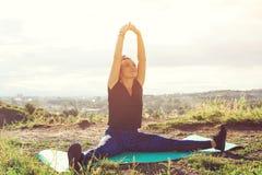 Giovane donna attraente che fa gli esercizi sulla collina sopra la città al tramonto immagini stock