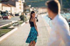 Giovane donna attraente che flirta con un uomo sulla via Donna sorridente civettuola che guarda indietro su un uomo bello Attrazi fotografie stock