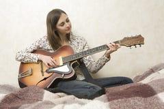 Giovane donna attraente che gioca chitarra fotografia stock