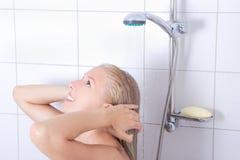 Giovane donna attraente che ha una doccia immagine stock