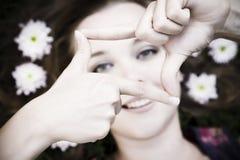 Giovane donna attraente che incornicia le sue mani Fotografia Stock