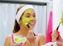 Giovane donna attraente che indossa cima rosa e fascia bianca, applicanti la miscela dell'avocado al fronte facendo uso della spa Fotografia Stock Libera da Diritti