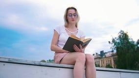 Giovane donna attraente che legge un libro all'aperto, cielo blu al fondo stock footage