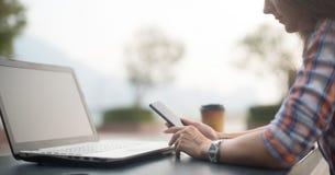 Giovane donna attraente che legge un messaggio di testo sul suo telefono cellulare Ragazza che si siede all'aperto facendo uso de Immagine Stock