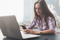 Giovane donna attraente che legge un messaggio di testo sul suo telefono cellulare Ragazza che si siede all'aperto facendo uso de Immagine Stock Libera da Diritti