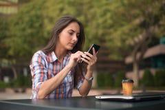Giovane donna attraente che legge un messaggio di testo sul suo telefono cellulare Ragazza che si siede all'aperto facendo uso de Fotografia Stock