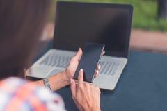 Giovane donna attraente che legge un messaggio di testo sul suo telefono cellulare Ragazza che si siede all'aperto facendo uso de Fotografia Stock Libera da Diritti