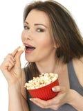 Giovane donna attraente che mangia e che gode del popcorn Immagine Stock Libera da Diritti