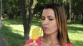 Giovane donna attraente che mangia il gelato su un bastone nel parco La ragazza mangia il gelato luminoso fra gli alberi verdi stock footage