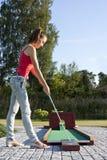 Giovane donna attraente che mette la sfera di golf sul verde Fotografie Stock