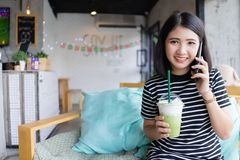 Giovane donna attraente che parla sul telefono cellulare al tè verde bevente della caffetteria mentre sedendosi sul sofà con facc immagini stock
