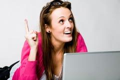Giovane donna attraente che pensa con il computer portatile Fotografia Stock