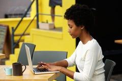 Giovane donna attraente che per mezzo del computer portatile fuori Immagine Stock