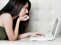 Giovane donna attraente che per mezzo del computer portatile nel paese fotografia stock