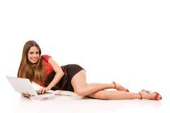 Giovane donna attraente che per mezzo del computer portatile sul pavimento Immagini Stock Libere da Diritti
