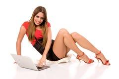Giovane donna attraente che per mezzo del computer portatile sul pavimento Fotografie Stock