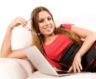Giovane donna attraente che per mezzo del computer portatile sullo strato Immagine Stock Libera da Diritti