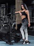 Giovane, donna attraente che per mezzo della bici di esercizio alla palestra Forma fisica Immagine Stock Libera da Diritti