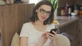 Giovane donna attraente che per mezzo dello smartphone con le cuffie video d archivio