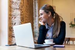 Giovane donna attraente che posa per un ritratto che si siede ad una tavola Fotografia Stock Libera da Diritti