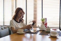 Giovane donna attraente che pulisce con attenzione i suoi occhiali da sole alla moda mentre sedendosi nella caffetteria moderna Immagine Stock