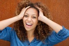 Giovane donna attraente che ride con le mani in capelli Immagini Stock