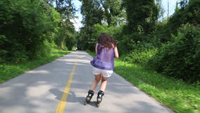 Giovane donna attraente che rollerblading nel parco un bello giorno soleggiato, facente slalom video d archivio