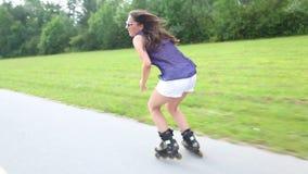 Giovane donna attraente che rollerblading nel parco un bello giorno soleggiato, facente slalom con i piedi stock footage