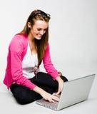 Giovane donna attraente che si distende con il computer portatile Fotografia Stock