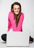 Giovane donna attraente che si distende con il computer portatile Fotografie Stock